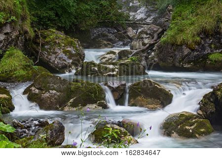 Fast mountain river flowing among mossy stones and boulders - cascade of small waterfalls