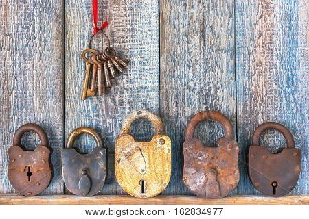 Old padlock and bunch of keys on a wooden boards background