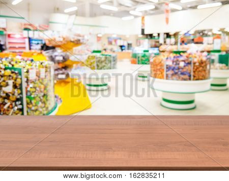 Wooden board empty table in front of of supermarket shelves. Perspective dark wood over blur in supermarket. Mock up for display or montage products