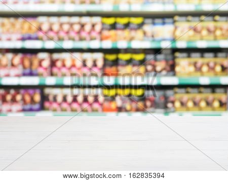 White wooden board empty table in front of of supermarket shelves with with hair-dye products. Mock up for display or montage products