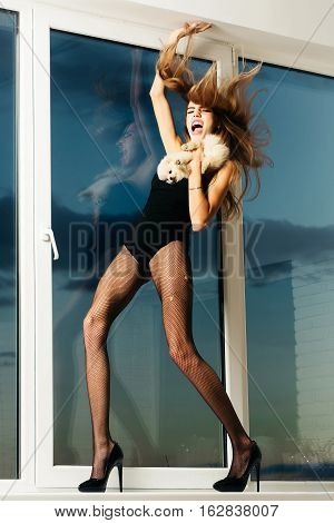 Pretty sexy girl cute slim shouting woman has pink lips with long hair and legs in black fishnet tights fashionable shoes and lingerie at window on blue sky background holds small dog or puppy pet