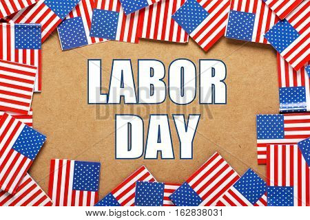 Flags of the United States of America arranged in a border around the words Labor Day, a public holiday to celebrate the contribution of workers