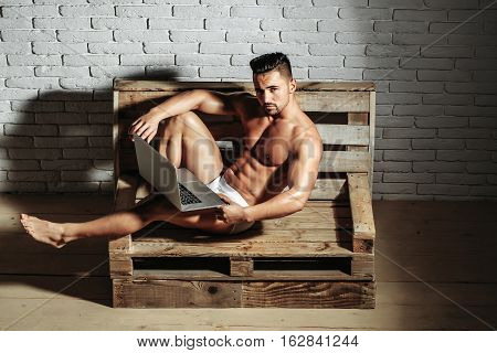 Handsome man or muscular macho bodybuilder with sexy muscle torso body with six packs and abs in sexi underpants uses laptop computer lying on wooden pallet sofa on white brick wall