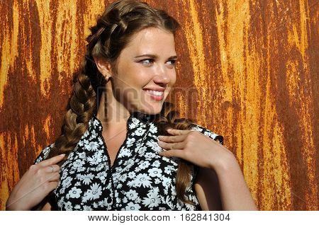 portrait of young attractive woman against old rusty wall background