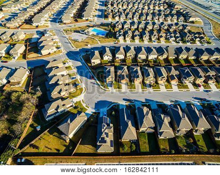 Aerial Drone Shot over Patterns of Architecture Sunset Suburban Homes North of Austin near Round Rock , Texas as Texas expands more and more homes are built in Modern Neighborhood Communities