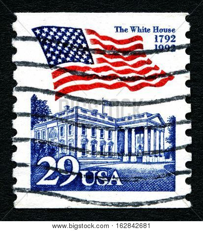 UNITED STATES OF AMERICA - CIRCA 1992: A postage stamp printed in the United States features waving US flag and the White House circa 1992