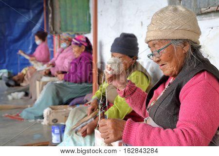 POKHARA, NEPAL - JANUARY 8, 2015: Tibetan women spinning wool at Tashi Palkhel Tibetan refugee camp