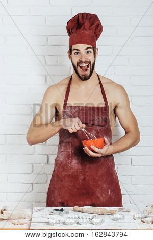 Excited handsome man or muscular cook baker in red chef hat and apron with flour on sexy muscle torso body with biceps triceps beats dough by whisk on kitchen wall