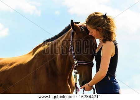 Jockey Young Girl Kissing And Hugging Brown Horse