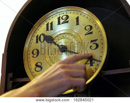 Human hand changes time on the old clock moving it forward in time