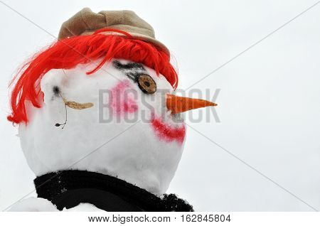 close-up of snow man with red wig black scarf and bonnet side view