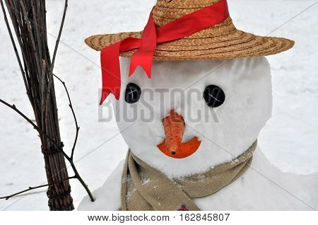 snowman closed in straw hat and scarf and holding broom