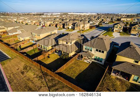 Sunset Suburban Homes North of Austin near Round Rock , Texas as Texas expands more and more homes are built in Modern Neighborhood Communities Bird's Eye View row after row of Cookie Cutter Houses low angle