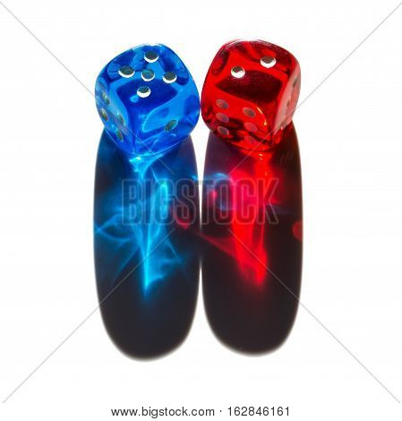 Red and blue transparent plastic dice with shiny shadows. Two tiny dice in sunlight with long colorful shadow cones. Light reflects in translucent material and shows exciting effects. Macro photo.