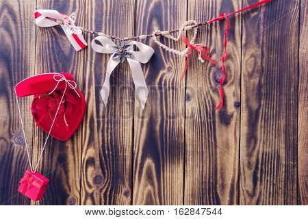 red heart with flower and gift and white bow and different ribbons hanging on a rope on a wooden background