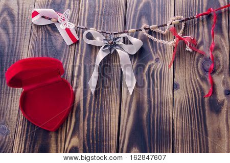 white bow and different ribbons hanging on a rope and open red box in a shape of heart on a wooden background