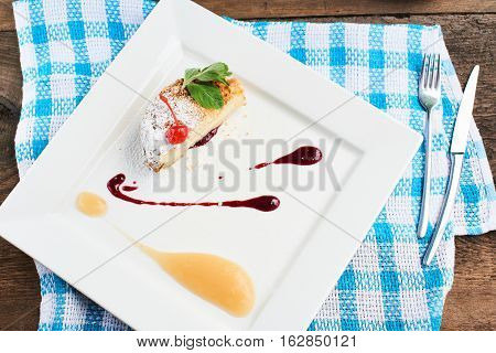 Top view of sweet dessert made of crumble with applesauce and cherry topping served on a white plate