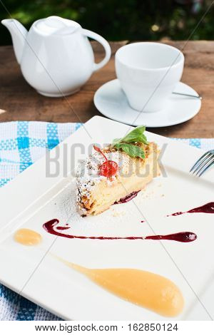 A sweet Breakfast of dessert crumble with applesauce and cherry topping served on a white plate and tea set