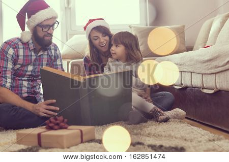 Young parents sitting on the living room floor next to a nicely decorated Christmas tree mother holding a baby girl in her lap and all together reading a fairy tale. Focus on the baby girl