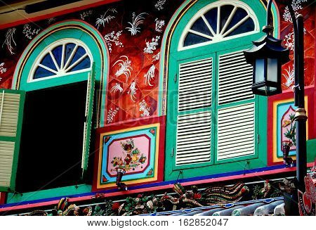 Melacca Malaysia - December 27 2006: Hand-painted facade of a Nyonya heritage house on Jonker Walk with arched windows featuring large fans and louvered shutters