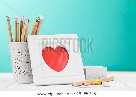 Love concept with photo frame, pencils and red heart. Horizontal with copy space. Office table.