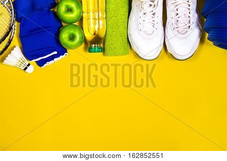 Flat lay of sport and healthy life concept with badminton, sport shoes, towel bottle of water, green apple and yoga mat. Healthy food concept.