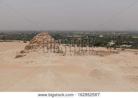 Step pyramid in the desert in Egypt near green mango plantation