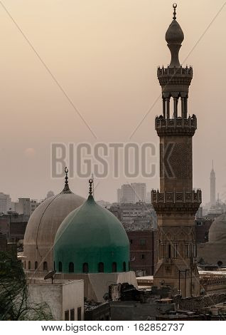 Sunset in dusty Cairo with mosque and minaret in Old Cairo district