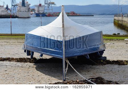 image of inverted wooden boat on the shore