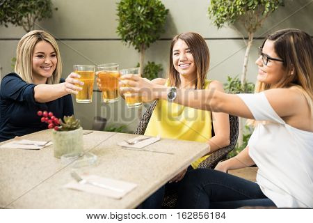 Beautiful Friends Making A Toast With Beer