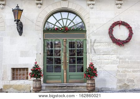 christmas wreath and doors with firry trees