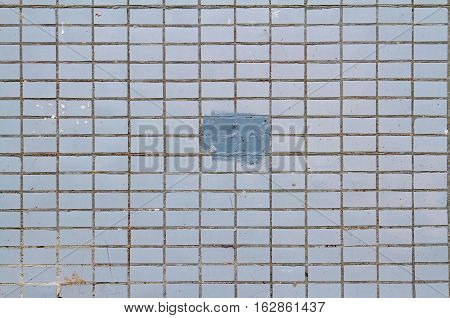 Mosaic tiles on the facade of a house. Architectural background made of blue mosaic wall with painted splotch