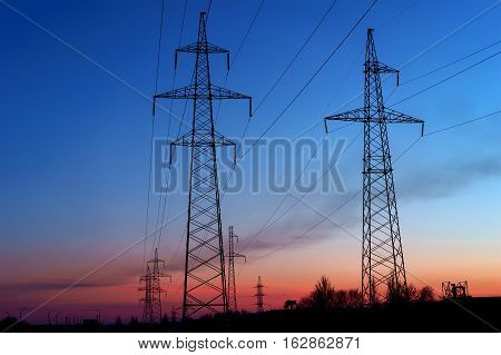 sunset with a silhouette of electricity pylon and power lines.