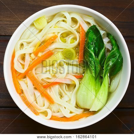 Vegetarian Asian rice noodle soup with bok choy carrots and spring onion photographed overhead with natural light