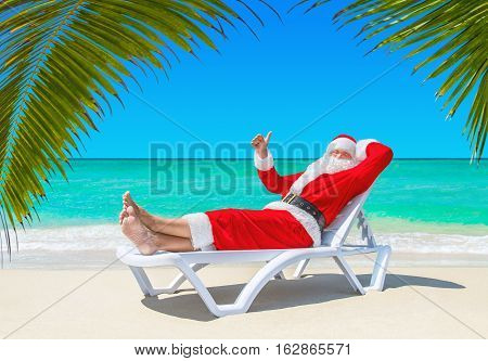 Santa Claus relaxing thumbs up gesturing on sunlounger at ocean tropical sandy beach under palm tree leaves. Merry Christmas and Happy New Year travel destinations for tropical vacations concept.