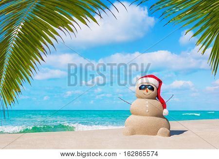Positive sandy snowman in red Santa Claus hat and eyeglasses at cloudy sunny ocean beach under palm tree leaves. Happy New Year and Merry Christmas travel destinations concept for tropical vacations.