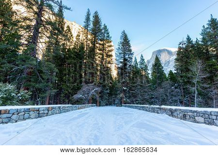 Snow covered bridge in winter in Yosemite National Park with Half Dome in the background