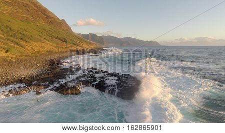 Aerial view of large waves washing up on rocky shore trail of Kaena Point on the northwest shore of Oahu