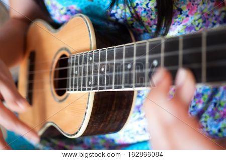Close up of woman strumming a ukulele, a popular Hawaiian musical instrument