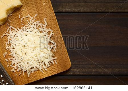 Freshly grated parmesan-like hard cheese on wooden board photographed overhead on dark wood with natural light (Selective Focus Focus on the grated cheese)