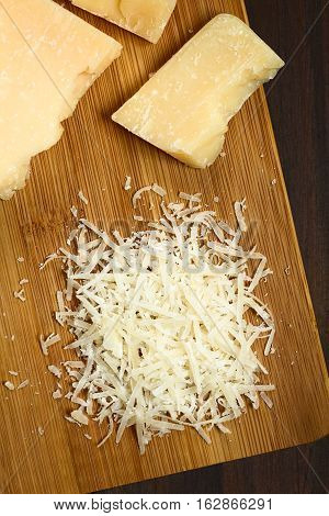 Freshly grated parmesan-like hard cheese with cheese pieces on wooden board photographed overhead with natural light