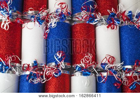 A close-up shot of a set of Crackers or otherwise known as a Bon Bons. A traditional cracker consists of a cardboard tube wrapped in a brightly decorated twist of paper with a gift in the central chamber.