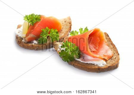 Two sandwiches with smoked salmon sauce and parsley on a white background