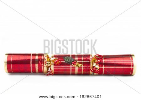 A studio shot of a Christmas Cracker or otherwise known as a Bon Bon. A traditional cracker consists of a cardboard tube wrapped in a brightly decorated twist of paper with a gift in the central chamber.
