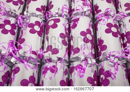A studio shot of Crackers or otherwise known as Bon Bons. A traditional cracker consists of a cardboard tube wrapped in a decorated twist of paper with a gift in the central chamber.