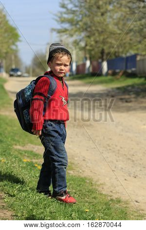 STINKA UKRAINE - APRIL 14 2016 - little rural schoolboy with a backpack walks from the school in village on April 14 2016 in Stinka