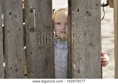 STINKA UKRAINE - APRIL 14 2016 - sad little girl looks out from the wicket door by hand on April 14 2016 in Stinka village.