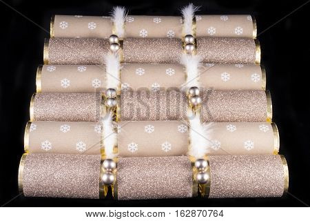 A studio shot of a set of Christmas Crackera or otherwise known as Bon Bons. A cracker consists of a cardboard tube wrapped in a decorated twist of paper with a gift in the central chamber.