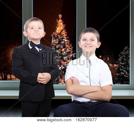 The younger brother in a suit and with a butterfly on her neck, and older brother in a shirt on a background of christmas trees outside the window