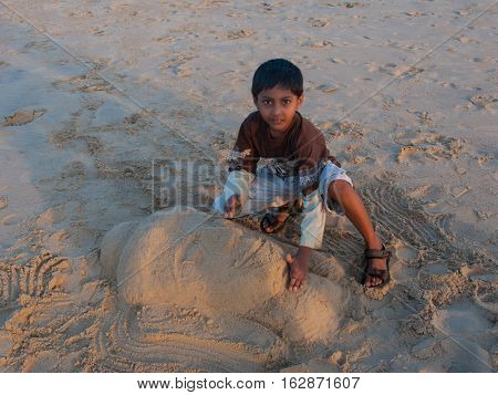 KERALA, INDIA. 25 January 2011:  Rural residents in daily life. Indian boy on the banks of the sand molds from the Buddha's head....  Chowara, Kerala, South-west India.